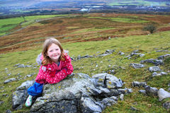 Junges blondes Mädchen, das auf Felsen in den Hügeln stillsteht Lizenzfreie Stockfotografie
