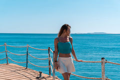 Junges blondes Mädchen, das auf Pier mit seascapeon Hintergrund aufwirft Lizenzfreie Stockfotos