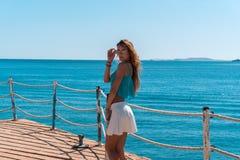 Junges blondes Mädchen, das auf Pier mit seascapeon Hintergrund aufwirft Stockfotografie