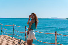 Junges blondes Mädchen, das auf Pier mit seascapeon Hintergrund aufwirft Lizenzfreies Stockfoto