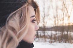 Junges blondes Mädchen, das den entfernten Wintersonnenuntergang betrachtet Stockbild