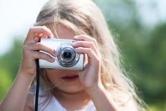 Junges blondes Mädchen, das Digitalkamera und das Fotografieren hält Lizenzfreie Stockfotos