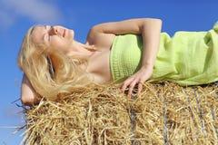 Junges blondes Mädchen, das im Heu liegt Lizenzfreie Stockfotos