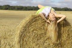 Junges blondes Mädchen, das im Heu liegt Stockfotografie