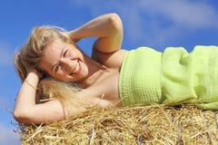 Junges blondes Mädchen, das im Heu liegt Stockfoto