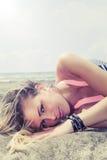 Junges blondes Mädchen, das im Meer liegt Lizenzfreie Stockbilder