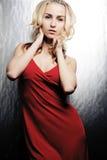 Junges blondes Mädchen, das im roten Kleid aufwirft. Stockbild