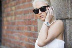 Junges blondes Mädchen, das im Telefon spricht Lizenzfreie Stockfotografie
