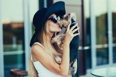 Junges blondes Mädchen, das kleinen Hund küsst Stockfotografie
