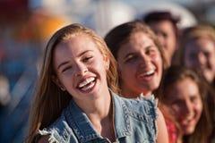 Junges blondes Mädchen, das mit Freunden lacht Lizenzfreie Stockfotos