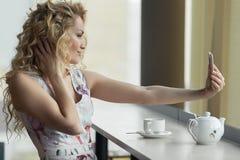 Junges blondes Mädchen, das Selbstporträt an ihrem intelligenten Telefon macht Stockbild