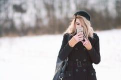 Junges blondes Mädchen, das Telefon draußen im Schnee betrachtet Stockfotografie