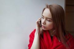 Junges blondes Mädchen, das am Telefon am Fenster sitzt, eingewickelt in einer roten Decke spricht Stockbilder