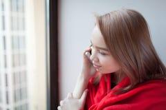 Junges blondes Mädchen, das am Telefon am Fenster sitzt, eingewickelt in einer roten Decke spricht Stockfoto