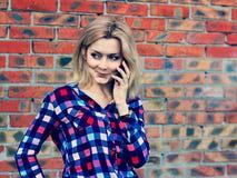 Junges blondes Mädchen, das am Telefon spricht Lizenzfreies Stockfoto