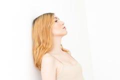 Junges blondes Mädchen, das weg mit ihrem Kopf stillsteht gegen schaut Stockfoto