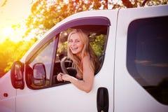 Junges blondes Mädchen, das weißes Auto an fahrend lacht Stockbild