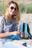 Junges blondes Mädchen in der schwarzen Sonnenbrille sitzt auf dem Strand und erhält Lizenzfreie Stockfotografie