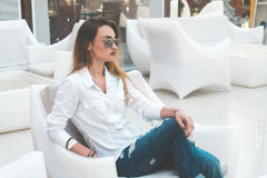 Junges blondes Mädchen in der weißen Kleidung, die draußen auf einem Stuhl aufwirft Stockbild