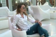 Junges blondes Mädchen in der weißen Kleidung, die draußen auf einem Stuhl aufwirft Lizenzfreie Stockfotografie
