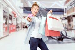 Junges blondes Mädchen hält ihre Einkaufstaschen Stockfotografie