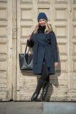 Junges blondes Mädchen im blauen Mantel mit Pelz in einer Strickmütze mit a Stockfotos