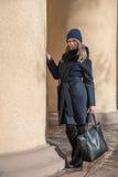 Junges blondes Mädchen im blauen Mantel mit Pelz in einer Strickmütze mit a Lizenzfreie Stockbilder