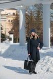 Junges blondes Mädchen im blauen Mantel mit Pelz in einer Strickmütze mit a Stockbild