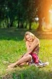 Junges blondes Mädchen im hellen bunten Kleid, welches das Lügen auf Gras im Sommerpark in den Strahlen des hellen Sonnenscheins  Stockfotografie