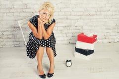 Junges blondes Mädchen im Kleid, das mit Borduhr sitzt Stockbilder