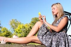 Junges blondes Mädchen im Park, der am Handy simst Stockfotografie