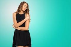 Junges blondes Mädchen im schwarzen Kleid Stockfotografie