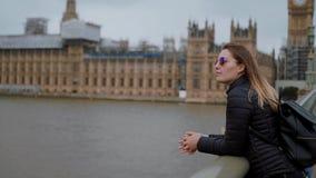 Junges blondes Mädchen in London - Westminster-Brücke und -Parlamentsgebäuden stock video