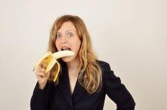 Junges blondes Mädchen mit Banane kleidete im Büroanzug an Stockfotos