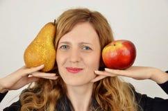 Junges blondes Mädchen mit der Birne und Apfel, zurechtgemacht im Büroanzug Stockbild