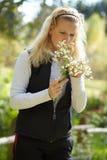 Junges blondes Mädchen mit einem Blumenstrauß der Gänseblümchen Lizenzfreie Stockbilder