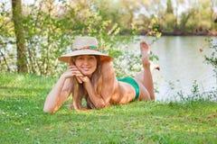 Junges blondes Mädchen mit einem Hut, der auf dem Gras liegt Stockfotografie