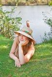 Junges blondes Mädchen mit einem Hut, der auf dem Gras liegt Lizenzfreies Stockbild