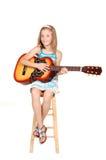 Junges blondes Mädchen mit Gitarre. Stockfotografie