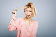 Junges blondes Mädchen mit Haar-Problemen Lizenzfreie Stockfotos