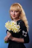 Junges blondes Mädchen mit Narzissen auf Blau Stockfotos