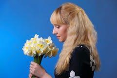 Junges blondes Mädchen mit Narzissen auf Blau Lizenzfreie Stockfotos