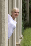 Junges blondes Mädchen schaut heraus von hinten eine Spalte Stockfotografie