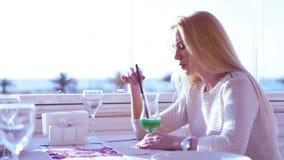 Junges blondes Mädchen trinkt ein Cocktail auf der sonnigen Terrasse eines tropischen Erholungsortes stock video footage