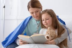 Junges blondes Mädchen und ein Freiwilliger, der sie liest stockbilder