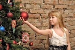 Junges blondes Mädchen und Weihnachtsbaum Stockbild