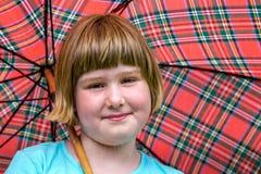 Junges blondes Mädchen unter Regenschirm im Regen Stockbild
