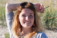 Junges blondes Mädchen warf ihre Hand mit einem Bleistift hinter ihren Kopf a Stockbild