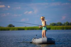 Junges blondes Mädchenfischen auf Boot Lizenzfreies Stockfoto