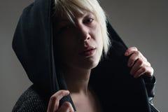 Junges blondes Mädchenporträt mit einem schwarzen Hoodie, Stockbilder